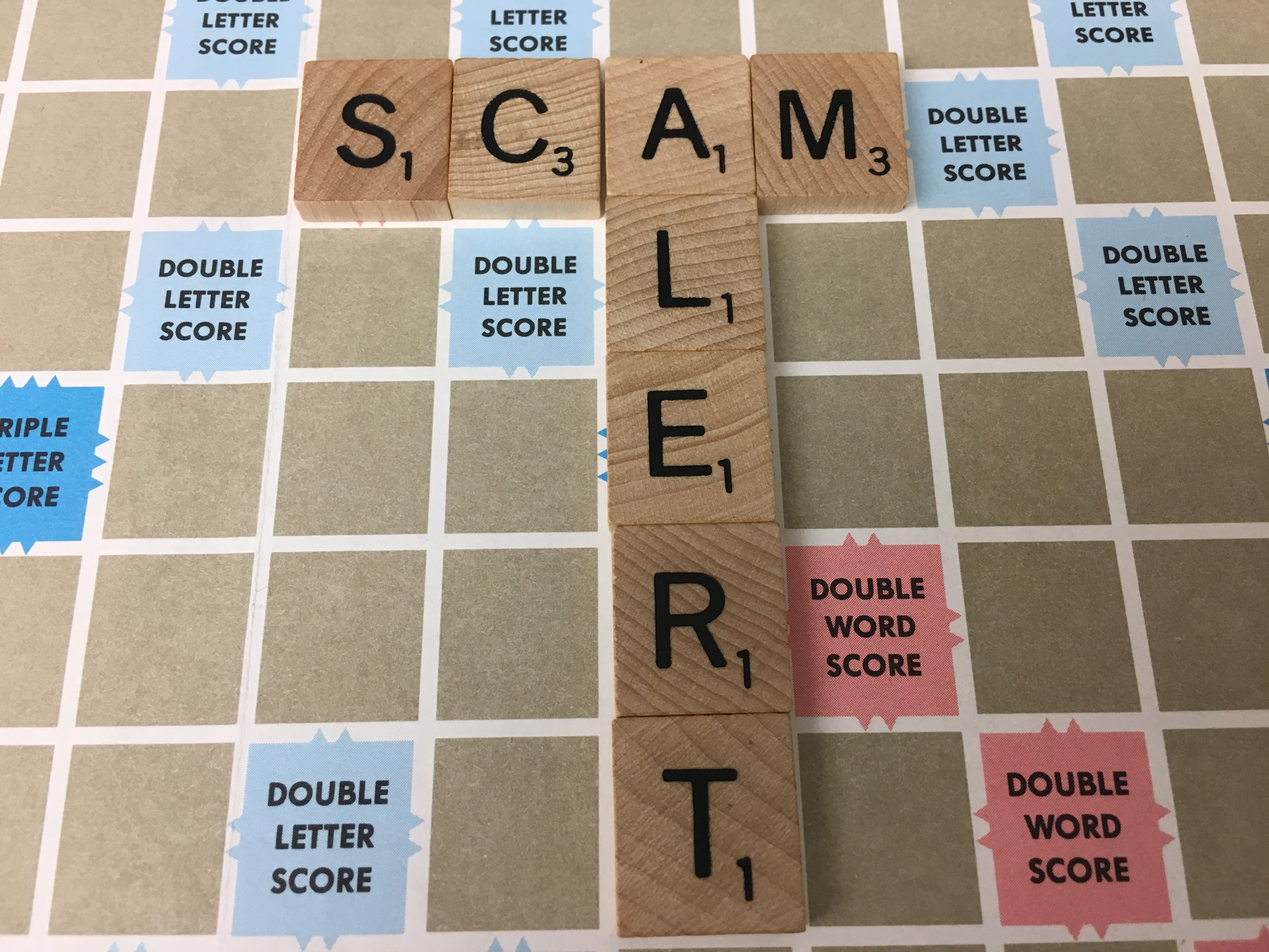Scam alert image spelled out in Scrabble tiles