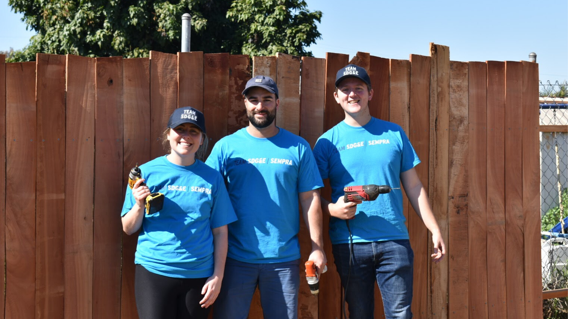 Team SDG&E volunteers pose in front of fence they built at Olivewood Gardens.