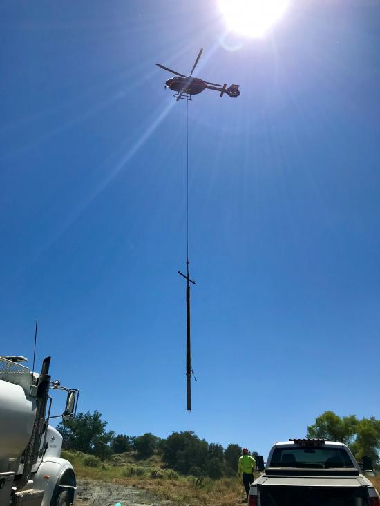 Helicopter setting a power pole